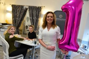 Image of Julie Managing director at Foundations holding a number 1 balloon inside the Academy